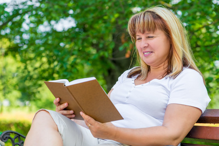 novel: mature woman reading a novel while sitting on a park bench