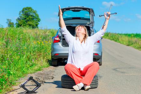 jack tar: praying female driver sitting at the wheel near the broken car Stock Photo