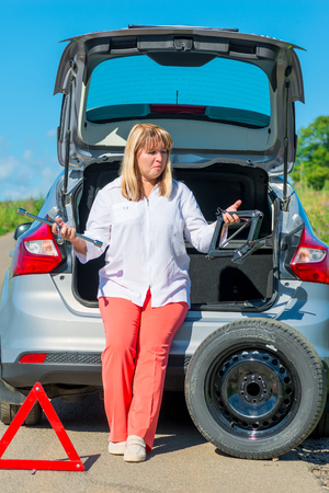 jack tar: confused mature woman driver near his car going to change wheels Stock Photo