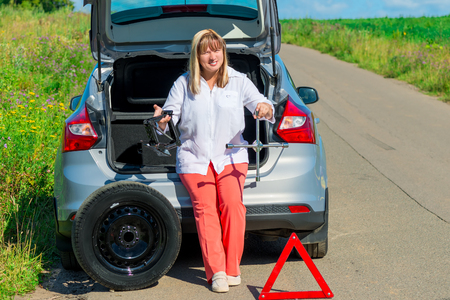 jack tar: portrait of a woman with tools for changing a wheel near the car Stock Photo