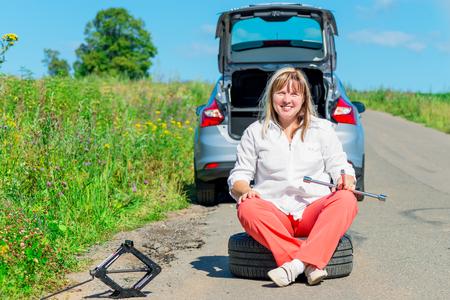 jack tar: Happy female driver at the wheel sitting near a broken car