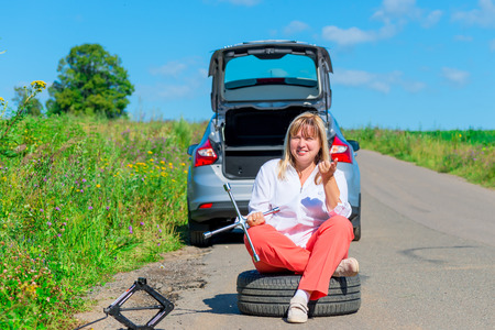 jack tar: woman sitting on the spare wheel with the tools on the road Stock Photo