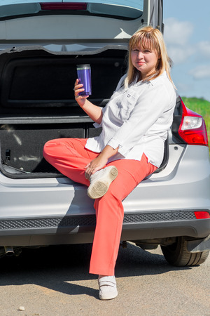 50 years old: woman 50 years old with a drink in the car to have a picnic Stock Photo