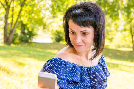 20 29 years: beautiful brunette photographing herself on the phone in the park Stock Photo