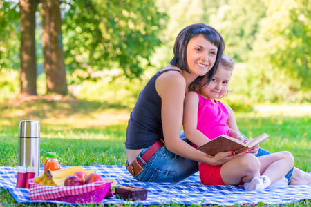 lawn grass: young mother with her daughter at a picnic