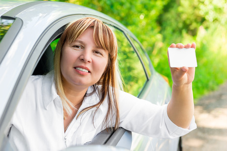 50 to 55 years: Joyful female driver showing a blank card Stock Photo