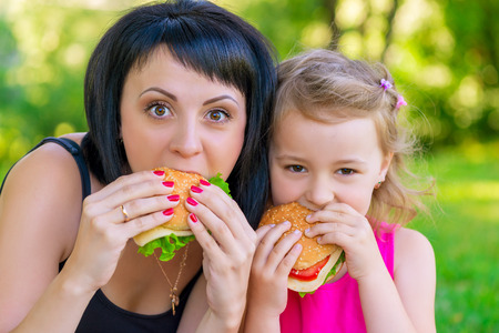 portrait of mother with her daughter in the park with burgers Imagens