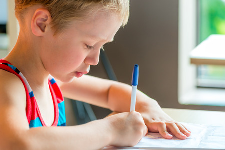 concentrated: concentrated boy draws a pen on paper Stock Photo