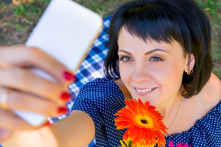 20 29 years: woman with flower photographing himself on the phone