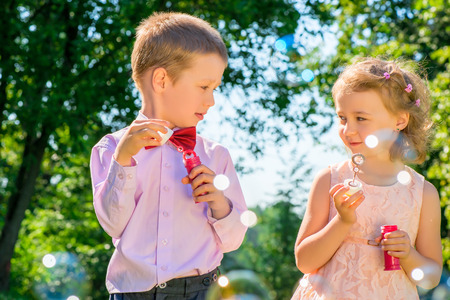 6 7 years: portrait of children with soap bubbles outdoors in the park Stock Photo