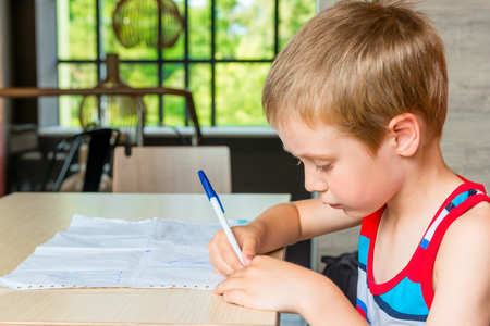only one boy: Portrait of a boy at the table drawing a pictures