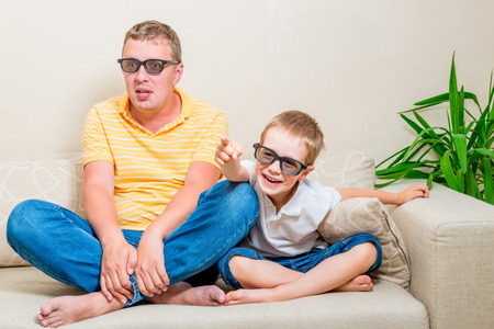 funny glasses: father and son watching a funny movie on TV in 3d glasses Stock Photo