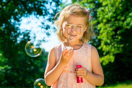 6 7 years: beautiful girl with soap bubbles in the park Stock Photo