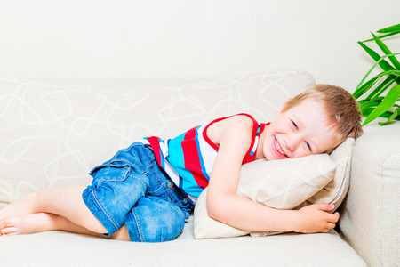 young boy smiling: portrait of a laughing little boy on the sofa with a pillow Stock Photo