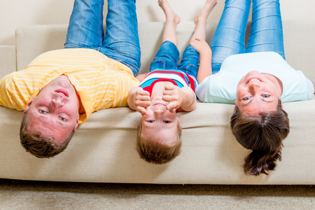 boy sitting: portrait of a happy family lying on couch head down