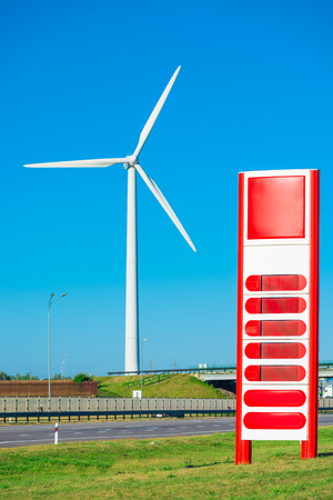 renewable energy resources: Windmill in the field and a petrol station near the road