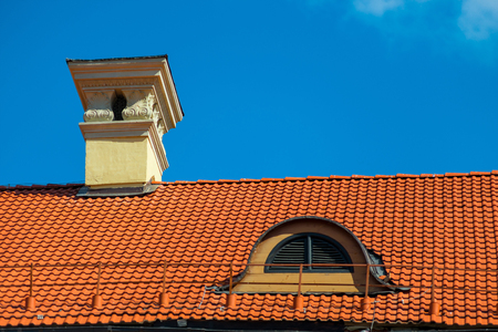 close up chimney: building roof covered with red tiles on a sunny day