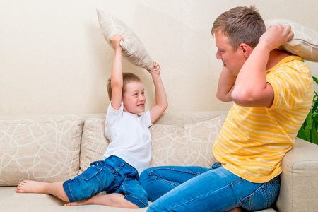 boy smiling: pillow fight on the couch is a fun game
