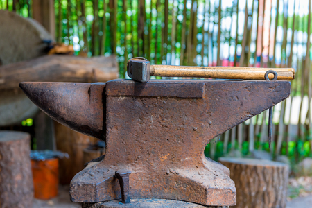 incus: heavy hammer on the anvil in the forge close up