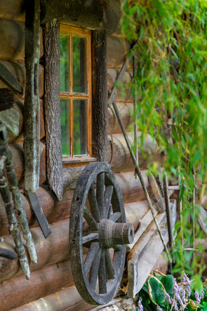 wheel house: wheel from an old cart near wooden rural house