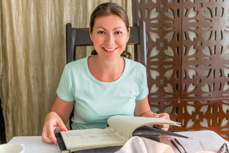 Ritratto di ragazza felice con un menu in un ristorante