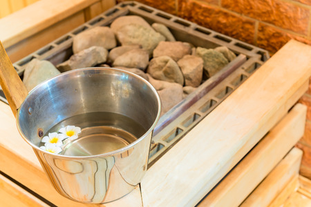 hot rock therapy: water with floating flowers and stones in the sauna Stock Photo