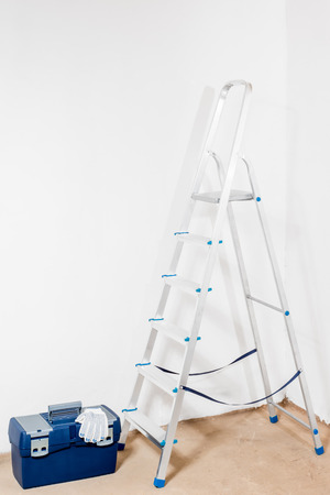 stepladder: white walls, stepladder and a tool box indoors