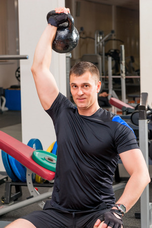 arms above head: athlete with heavy weights above his head at arms length