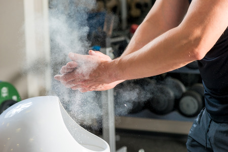weightlifter: male weightlifter processes hands talcum powder against sliding Stock Photo