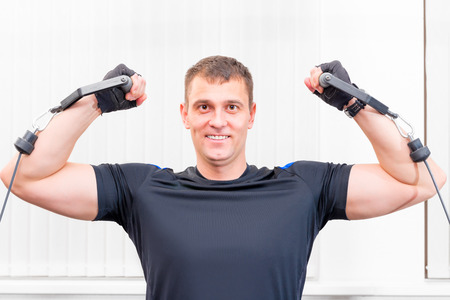 sports hall: pretty strong man is engaged in a sports hall