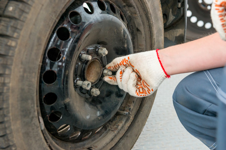 tire fitting: hand in a glove unscrews the nuts on the wheel