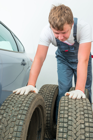 tire fitting: mechanic inspects the automobile tires before installation