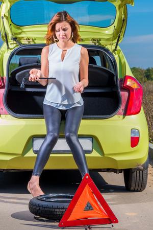 Девушка на корточках возле авто