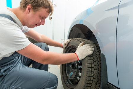 tire fitting: mechanic installs on the car winter tires in garage