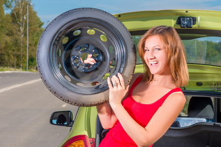 breakage: cheerful girl with a spare wheel near the car