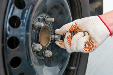 tire fitting: mans hand unscrews the nuts on the car wheel, close-up shot Stock Photo