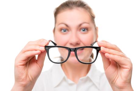 poor eyesight: woman with poor eyesight wears glasses, focus on glasses