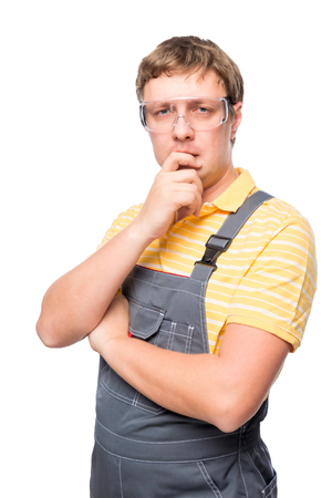 boilersuit: a man in overalls and protective glasses thinking on a white background Stock Photo