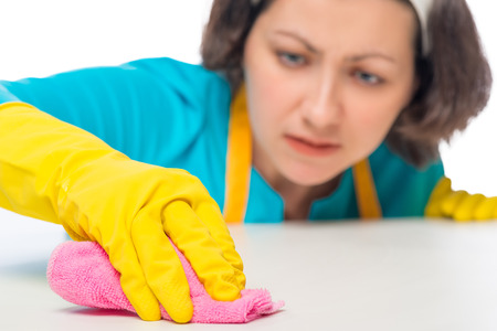 hand rubbing: woman meticulously rubbing the white table a rag, hand closeup