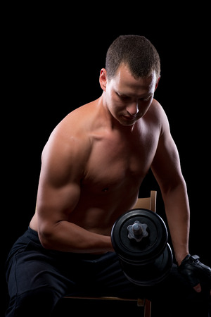 heavy weight: Muscled exercising with heavy weight on the chair Stock Photo