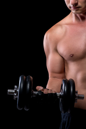 muscled: heavy dumbbells in the hands of a young Muscled Stock Photo