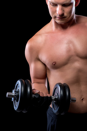 picks: muscular sexy guy picks up a heavy dumbbell