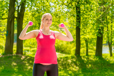 athletic girl maintains shape during pregnancy, exercise in the park