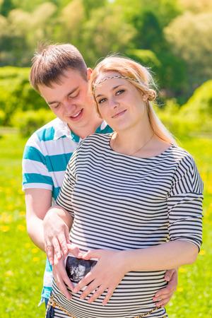 los padres jóvenes la celebración de las fotos, con el resultado de Uzi cerca del abdomen