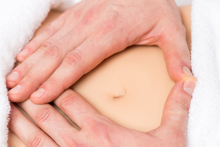 bellybutton: male hands in a heart shape on the abdomen of a pregnant woman close-up