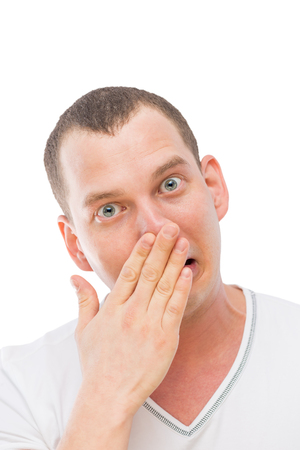 a young man makes a face, rubbing his nose with his hand isolated Stock Photo