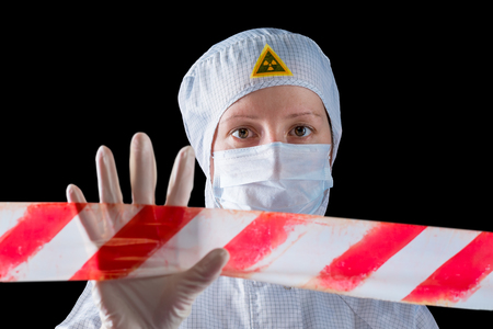 woman in protective clothing working in the infected area, shows fencing the area Stock Photo