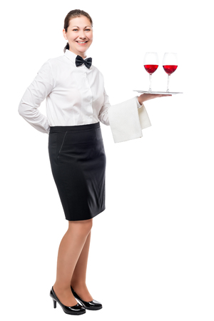 Portrait of a young waitress with glasses of red wine on a tray isolated in full length Stock Photo