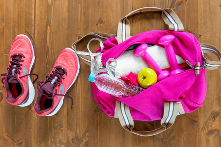 open sports bag and pink running shoes on a wooden floor top view