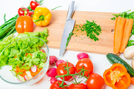 a wooden cutting board, knife and fresh vegetables for salad on a table close up Stok Fotoğraf - 75246280